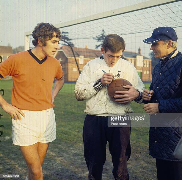 English actor and comedian Peter Cook watches Tottenham Hotspur goalkeeper Pat Jennings sign a football for a fan in 1968
