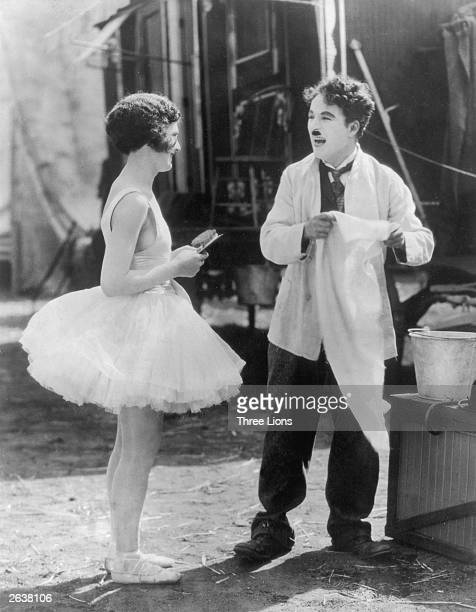 English actor and director Charlie Chaplin laughing with an actress during a scene from the silent film 'The Circus'