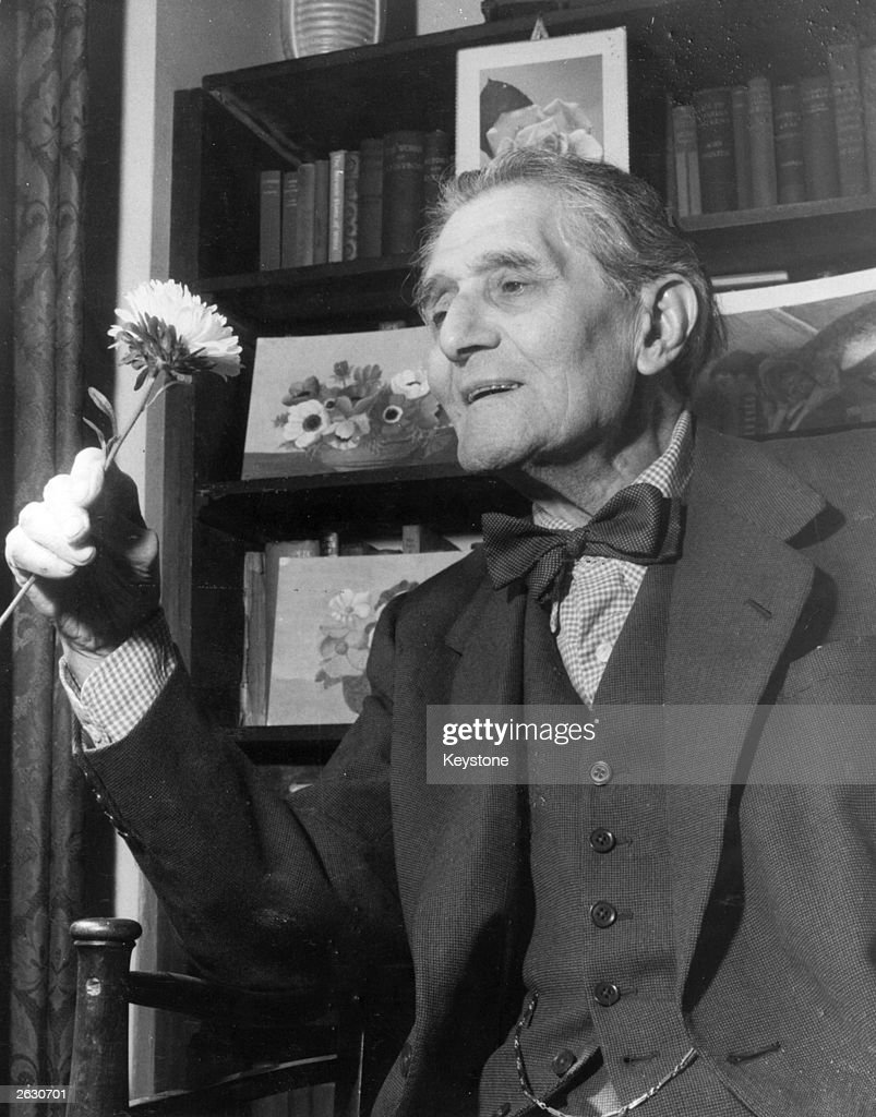 English actor and mimic Bransby Williams (1870 - 1961) at his home in Herne Hill on the eve of his 89th birthday, admiring a bunch of flowers sent by a fan.