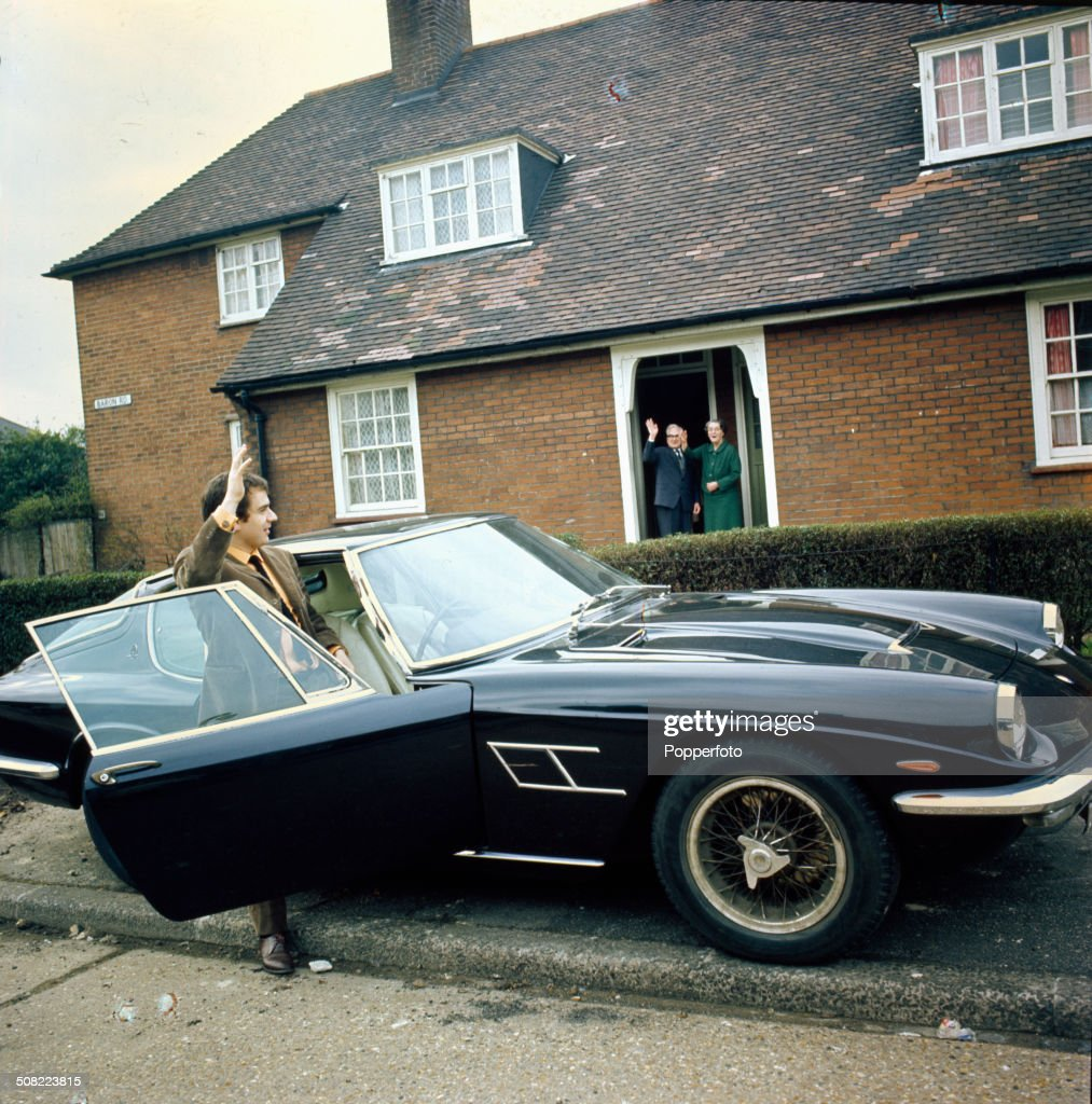 English actor and musician Dudley Moore waves to his parents Ada and John from the door of his black Maserati Mistral car in 1966