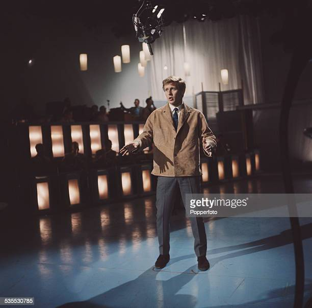 English actor and singer John Leyton performs on stage during the recording of a television show in 1962