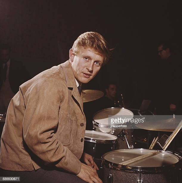 English actor and singer John Leyton posed at a drumkit on stage in 1962