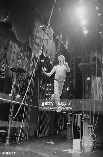 English actor and singer Michael Crawford pictured balancing on a tightrope whilst juggling balls on stage at a rehearsal at the Palladium in London...