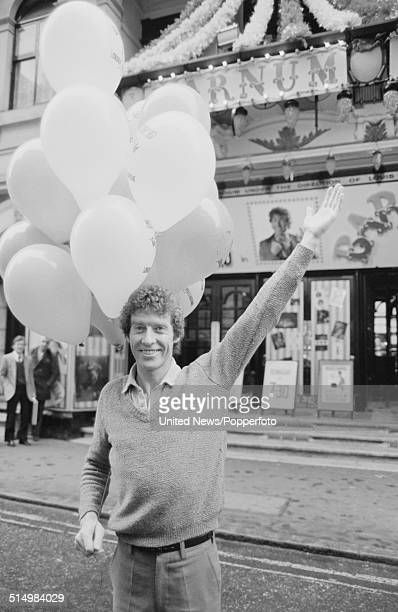 English actor and singer Michael Crawford posed holding balloons outside the Palladium in London during the production of the musical Barnum in...