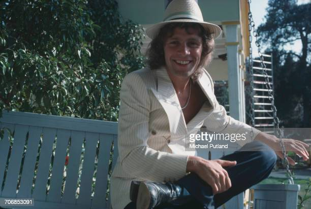 English actor and singer Paul Nicholas posed sitting on a swing seat on the set of the 'Sgt Pepper's Lonely Hearts Club Band' film USA October 1977