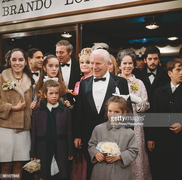 English actor Charlie Chaplin pictured centre with members of his family at the premiere of the film 'A Countess from Hong Kong' at the Carlton...