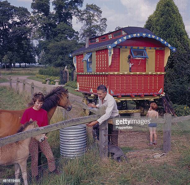 1968 English actor Donald Hewlett at home with his wife and child in front of a Gipsy caravan in 1968