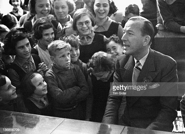 English actor dramatist and songwriter Noel Coward singing and playing the piano to children at the Actors Orphanage at Silverlands Chertsey Surrey...