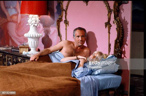 English actor Ian Hendry pictured in bed with Swedish actress Britt Ekland in a scene from the television drama series 'Armchair Theatre A Cold...