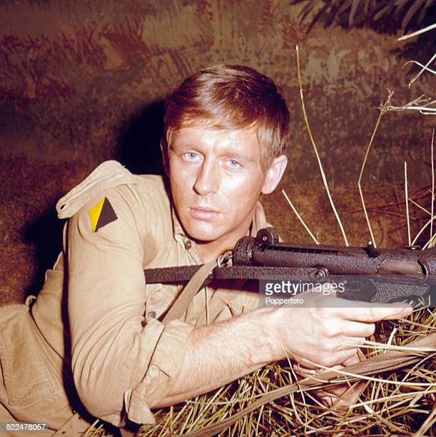 English actor John Leyton pictured holding a rifle on the set of the film 'Guns At Batasi' in 1964