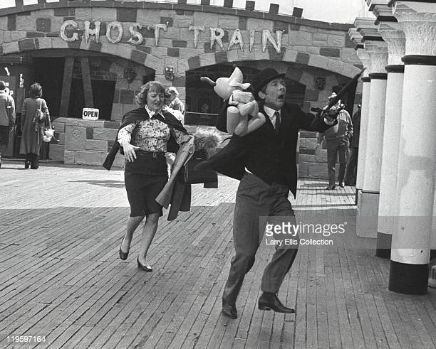 English actor Kenneth Williams and actress Patsy Rowlands on Brighton Pier for the filming of 'Carry On at Your Convenience' Brighton 1971