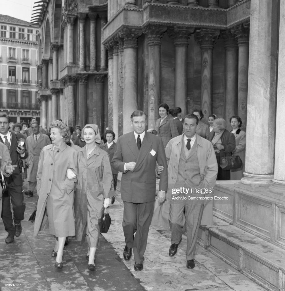 English actor Laurence Olivier with his wife Vivien Leigh and the couts of Modrone having a walk in St. Mark Square, Venice, 1957.