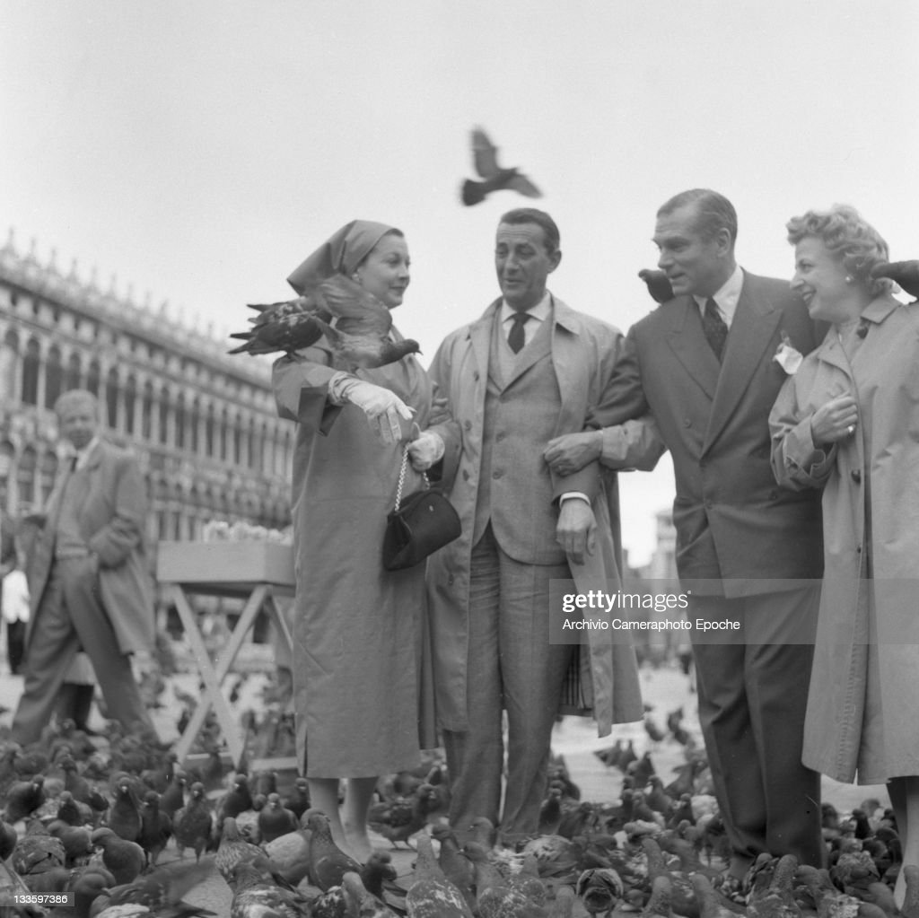 English actor Laurence Olivier with his wife Vivien Leigh and the couts of Modrone feeding the pigeons in St. Mark Square, Venice, 1957.