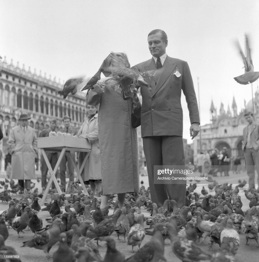 English actor Laurence Olivier with his wife Vivien Leigh portrayed while feeding pigeons in St. Mark Square, Venice, 1957.