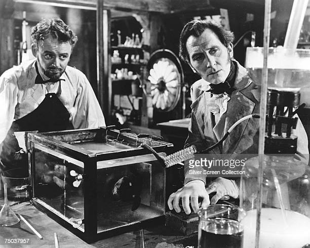English actor Peter Cushing as Baron Victor Frankenstein and Robert Urquhart as Paul Krempe in the Hammer horror film 'The Curse of Frankenstein' 1957