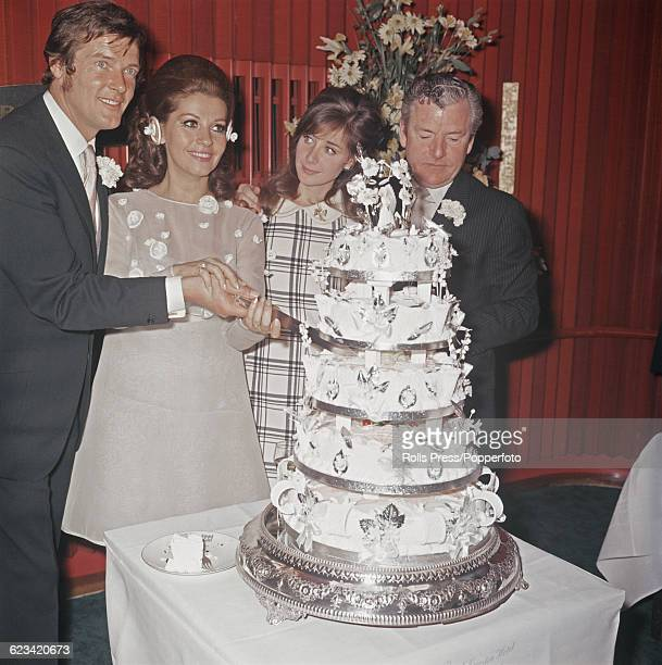 English actor Roger Moore and his wife Luisa Mattioli cut their five tiered wedding cake watched by best man Kenneth More and guest Angela Douglas...
