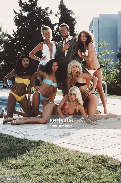 English actor Roger Moore as 007 surrounded by bikiniclad women in a publicity still for the James Bond film 'For Your Eyes Only' February 1981