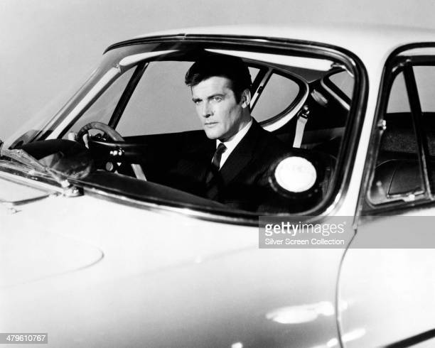 English actor Roger Moore as Simon Templar in a promotional portrait at the wheel of a Volvo P1800 sports car for the British spy thriller TV series...