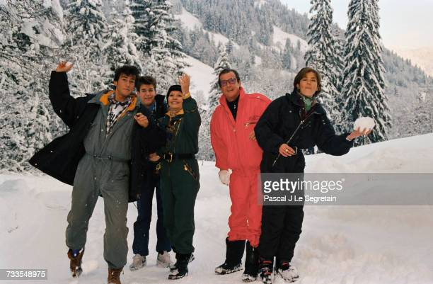 English actor Roger Moore has a snowball fight with his family while on vacation in Gstaad Switzerland Left to right are sons Geoffrey and Christian...