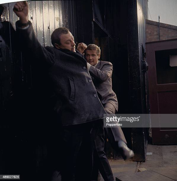 English actor Roger Moore in character as 'Simon Templar' fighting another man in a scene from the television series 'The Saint' in 1967