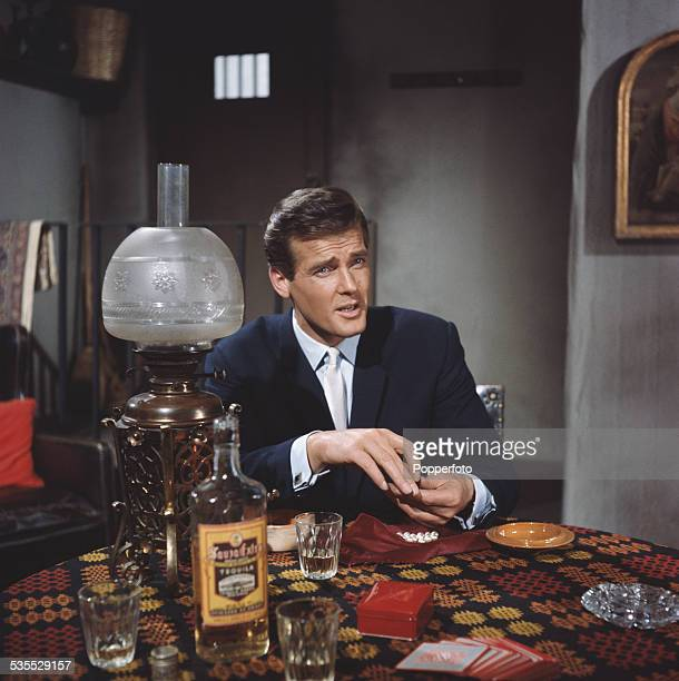 English actor Roger Moore pictured in character as Simon Templar in a card game scene from the television drama series The Saint at Elstree Studios...