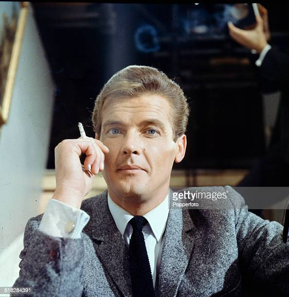 English actor Roger Moore pictured smoking a cigarette on the set of the television drama series 'The Saint' in 1965