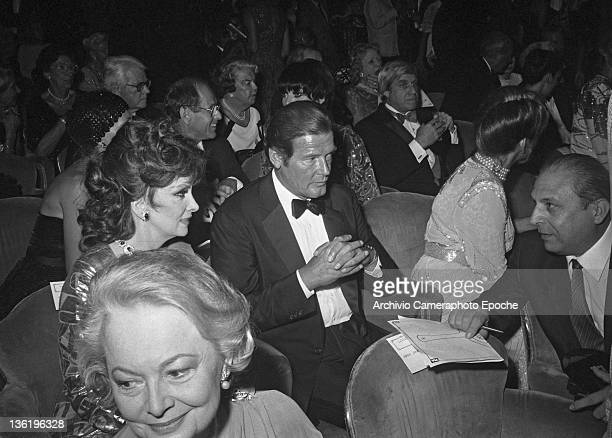 English actor Roger Mooresitting among the audience of the 'Teatro La Fenice' with Gina Lollobrigida Liza Minnelli and Olivia De Havilland Tribute To...