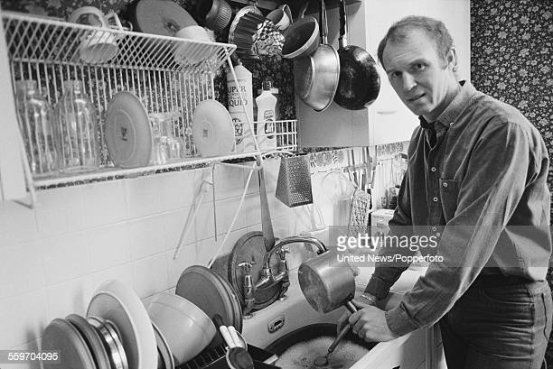 English actor Tim PigottSmith pictured washing up saucepans in his kitchen at home in Highgate London on 8th February 1984