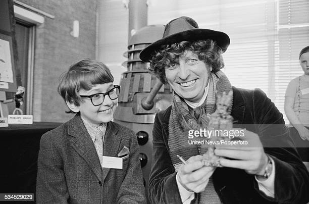 English actor Tom Baker dressed in character as The Doctor from the BBC science fiction television series Doctor Who pictured with a young winner of...