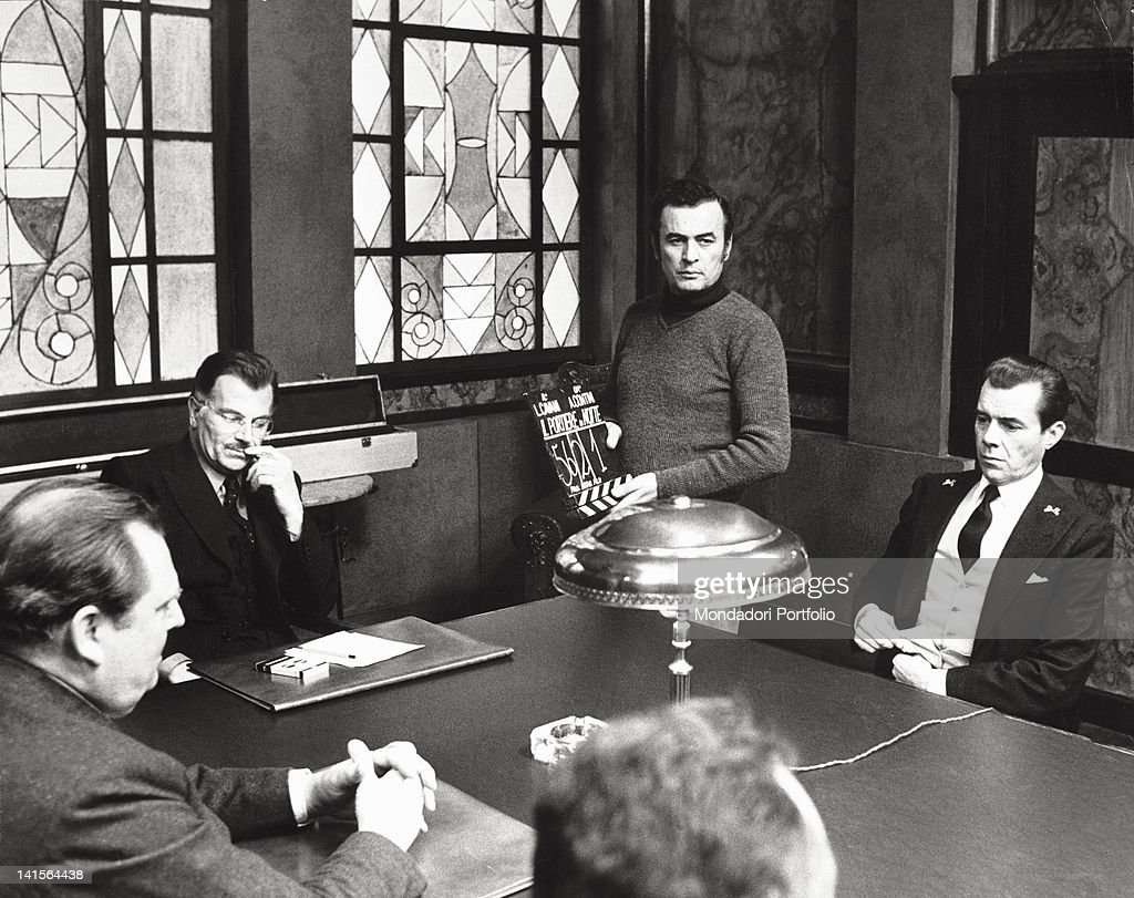 English actors Dirk Bogarde and Geoffrey Copleston playing with Italian actor Gabriele Ferzetti in 'The Night Porter' ('Il portiere di notte'). Rome, 1974