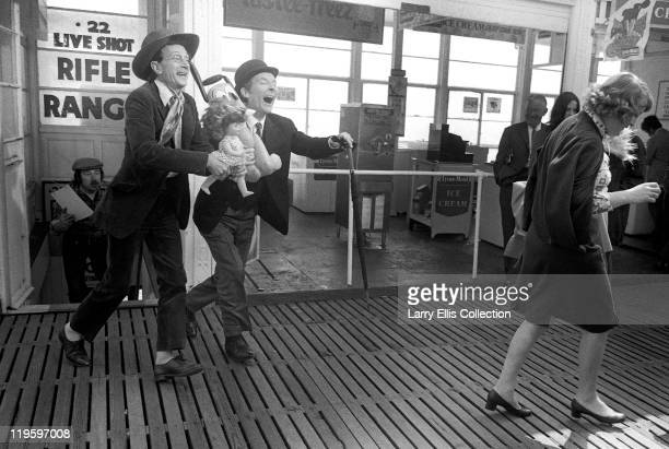 English actors Kenneth Williams and Charles Hawtrey with actress Patsy Rowlands on Brighton Pier for the filming of 'Carry On at Your Convenience'...