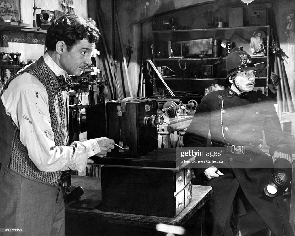 English actors <a gi-track='captionPersonalityLinkClicked' href=/galleries/search?phrase=Robert+Donat&family=editorial&specificpeople=210842 ng-click='$event.stopPropagation()'>Robert Donat</a> (1905 - 1958, left) as William Friese-Greene, and <a gi-track='captionPersonalityLinkClicked' href=/galleries/search?phrase=Laurence+Olivier&family=editorial&specificpeople=80991 ng-click='$event.stopPropagation()'>Laurence Olivier</a> (1907 - 1989) as a police officer, in 'The Magic Box', directed by John Boulting at Elstree Studios Hertfordshire, 1951.