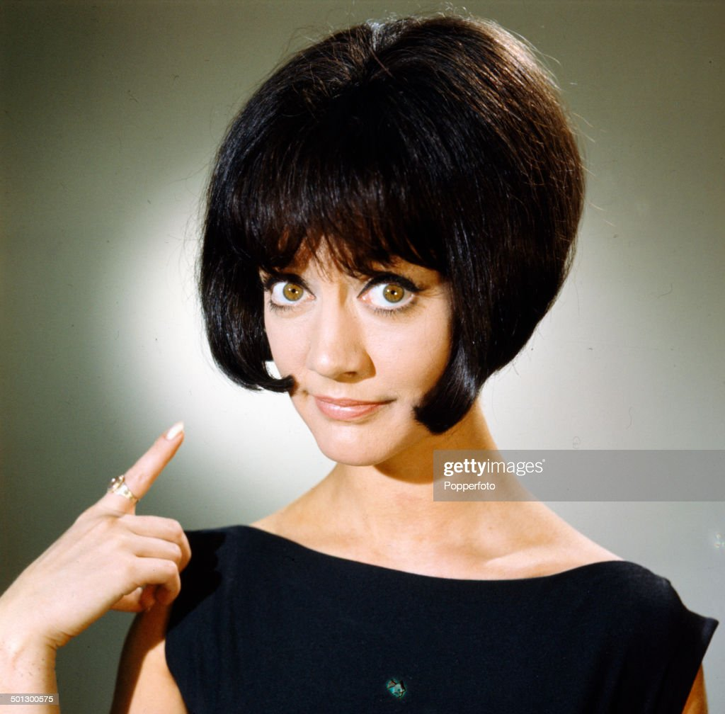 English actress Amanda Barrie pointing to her bob cut hairstyle in 1966.