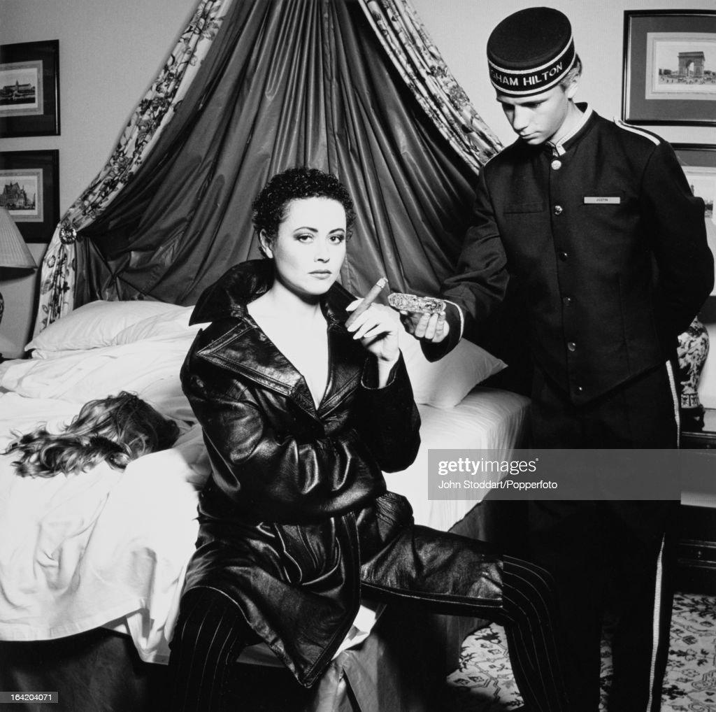 English actress Amanda Mealing smokes a cigar at the Birmingham Hilton, while a bellboy holds an ashtray, circa 2000.