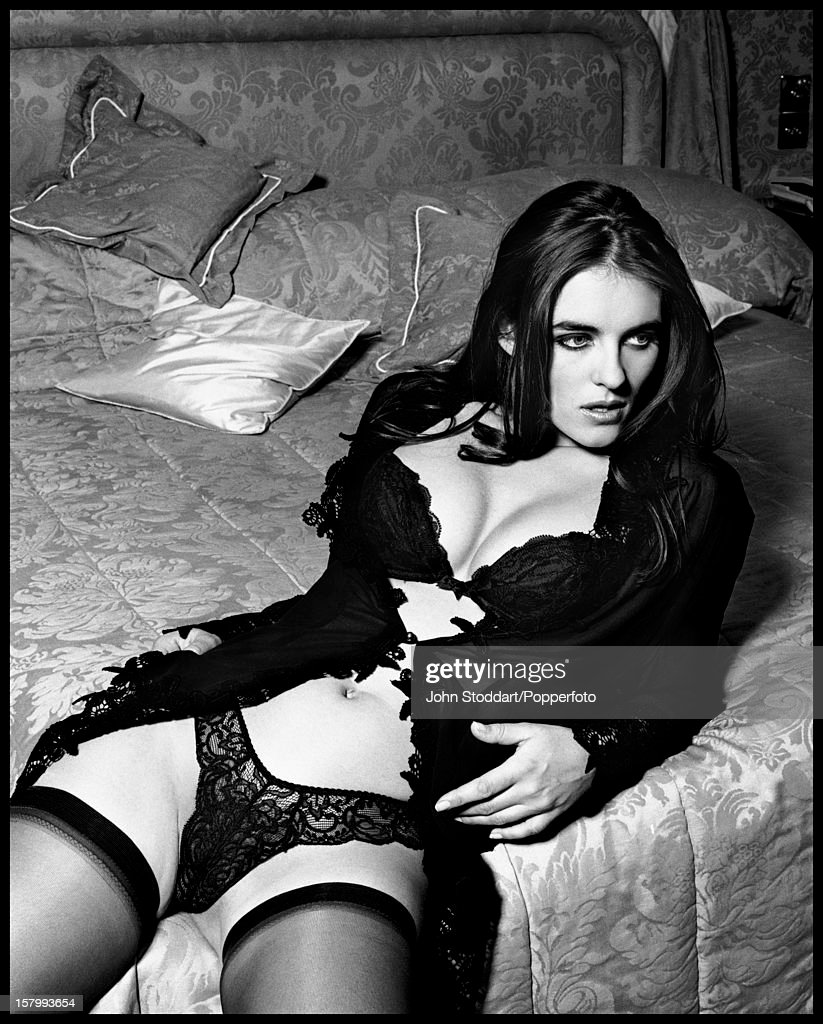 English actress and model Elizabeth Hurley reclines on a bed in black lace lingerie London 1992
