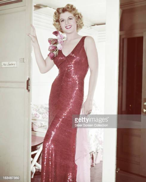 English actress Angela Lansbury wearing a red evening dress in the doorway of her dressing room circa 1945