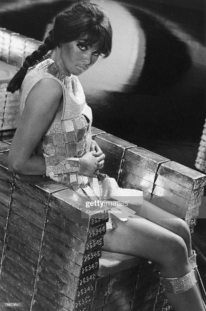 English actress Caroline Munro sitting on a throne of fake gold ingots in a promotional still for 'Casino Royale', directed by Val Guest et al, January 1967.