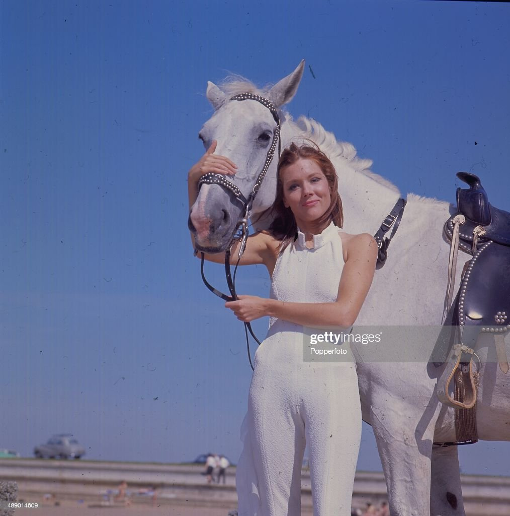 1967 - English actress <a gi-track='captionPersonalityLinkClicked' href=/galleries/search?phrase=Diana+Rigg&family=editorial&specificpeople=206289 ng-click='$event.stopPropagation()'>Diana Rigg</a> in her role as 'Emma Peel' from the television series 'The Avengers' stands with a white horse on Camber Sands, England in 1967.