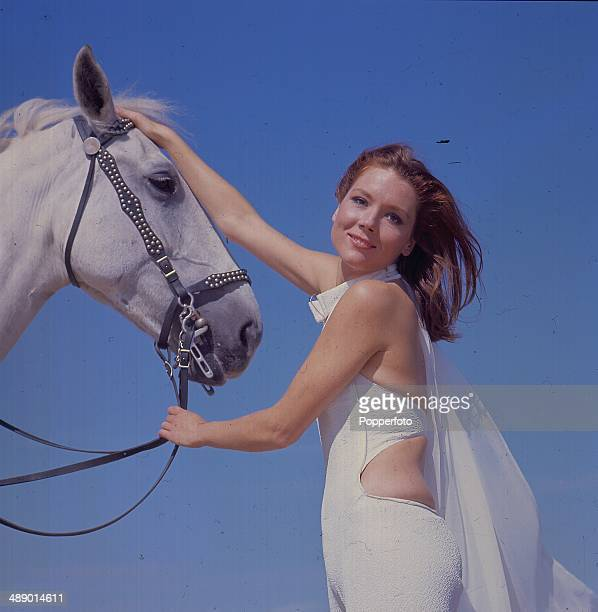 1967 English actress Diana Rigg in her role as 'Emma Peel' from the television series 'The Avengers' stands with a white horse on Camber Sands...