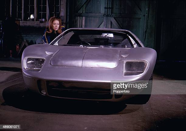 1968 English actress Diana Rigg pictured beside an aluminium body Ford GT40 in a scene from the television series 'The Avengers' in 1968