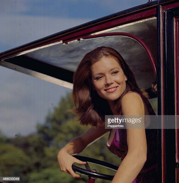 English actress Diana Rigg pictured in the driving seat of a vintage car in a scene from the television series 'The Avengers' in 1967