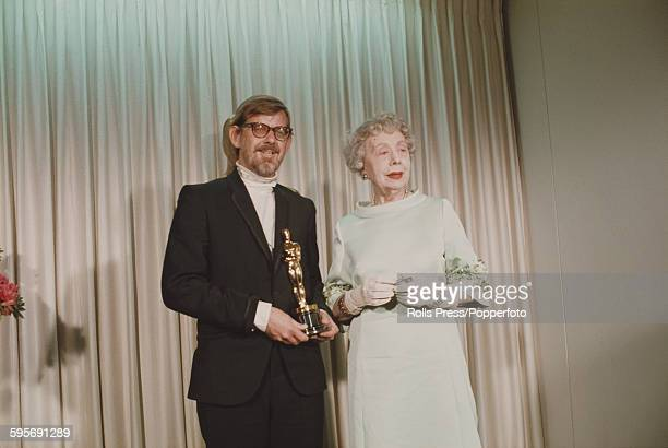 English actress Edith Evans pictured standing with American film editor Hal Ashby at the 40th Academy Awards at the Santa Monica Civic Auditorium in...