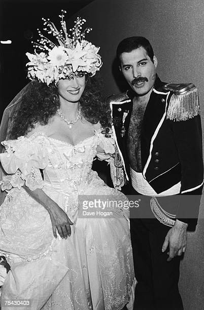 English actress Jane Seymour in a white ballgown with singer Freddie Mercury of British rock group Queen in a militarystyle dress uniform during...