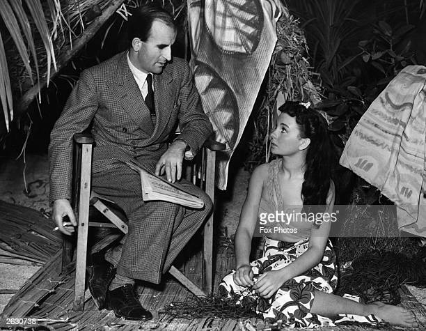 English actress Jean Simmons discusses the script for her latest film 'The Blue Lagoon' with director Frank Launder The two are at Pinewood Studios...