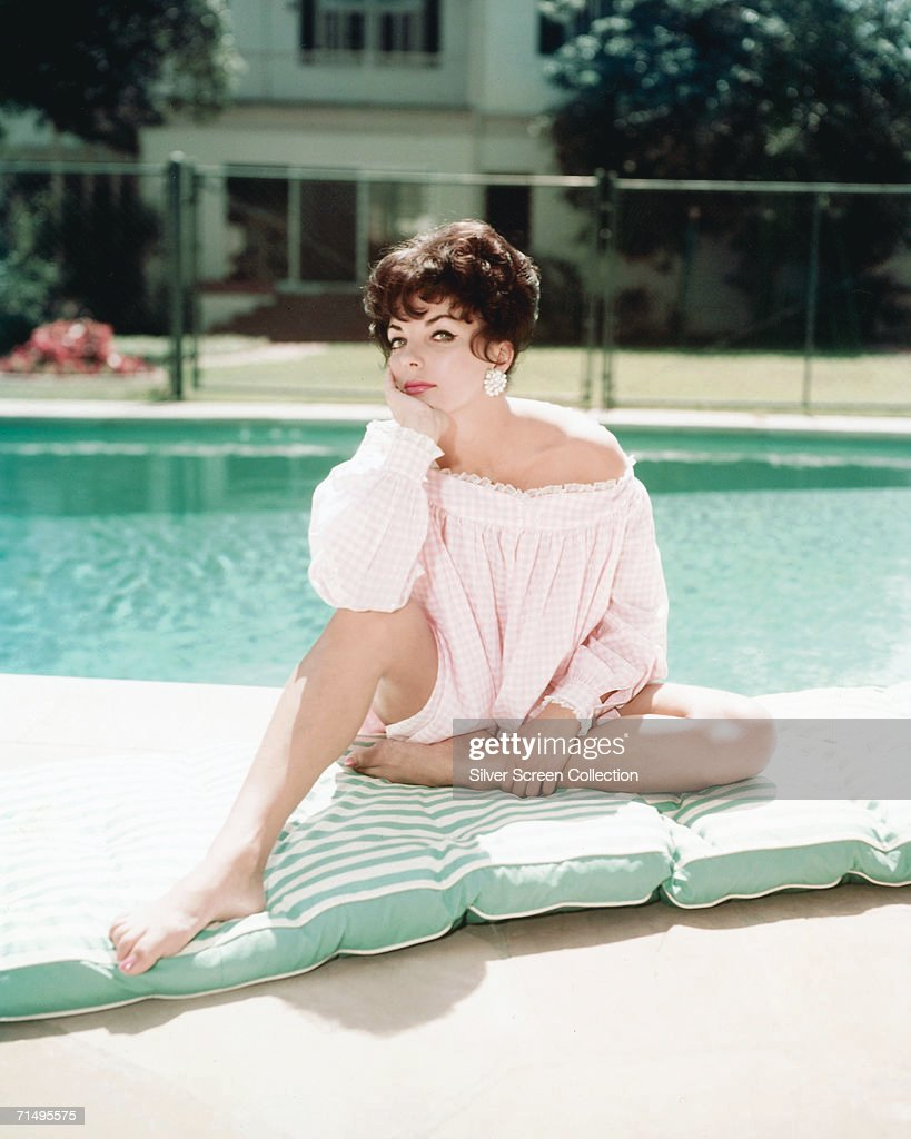 English actress Joan Collins sits on a mattress by a swimming pool, circa 1960.