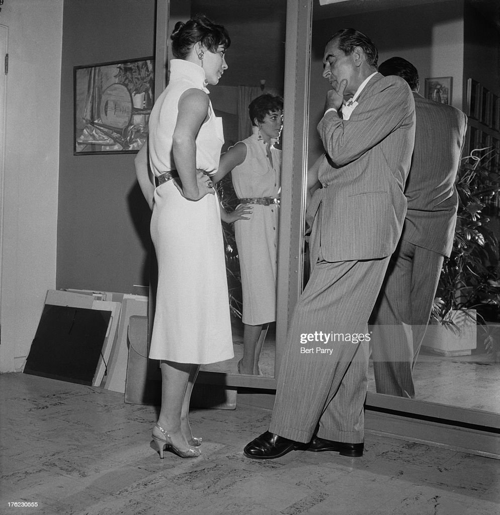 English actress Joan Collins talks with a man at a film studio 15th August 1955