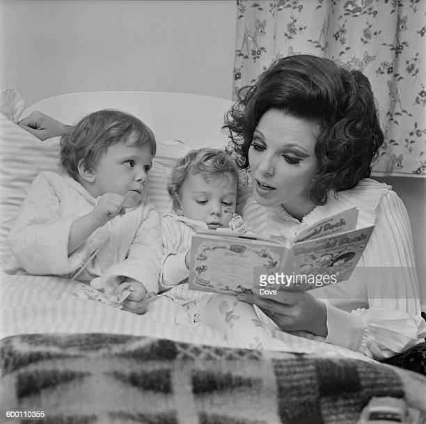 English actress Joan Collins the wife of actor and singer Anthony Newley reading a Donald Duck book to their two children Tara and Sacha UK 18th...
