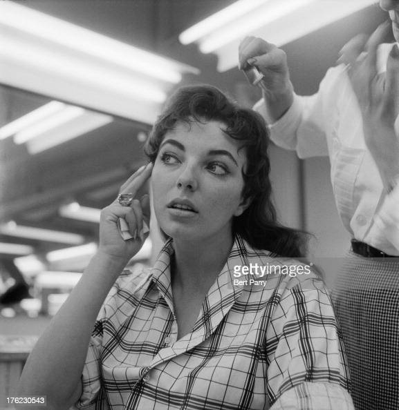English actress Joan Collins tilts her head as a stylist adjusts her hair in a film studio 15th August 1955