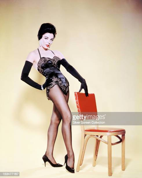 English actress Joan Collins wearing a black lacetrimmed bustier and black evening gloves circa 1955