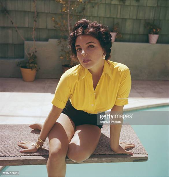 English actress Joan Collins wearing a yellow blouse and shorts circa 1960